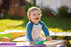Little chubby baby boy laughs, sitting in the sandbox in the sum Royalty Free Stock Photo