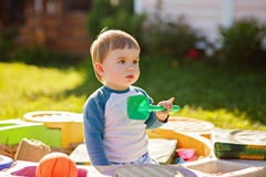 Little chubby toddler boy playing in the sandbox, holding a shov Stock Image