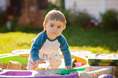 Little chubby toddler boy playing in the sandbox in the summer i Royalty Free Stock Photo