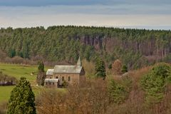 Little church in Ardennes landscape with meadows and pine trees. Liege, Belgium Stock Photos