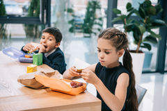 Little classmates eating lunch at break in school Stock Image