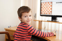 Little clever boy playing chess online Royalty Free Stock Image