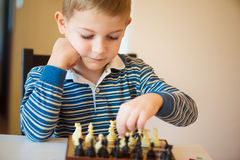 Little clever boy thinking with chess Stock Image