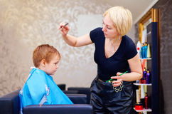 Little client, boy having haircut at hair salon Stock Photo