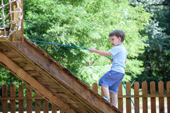 Little climber takes the rope bridge. Boy has fun time, kid climbing on sunny warm summer day Royalty Free Stock Photo