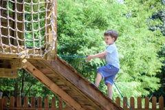 Little climber takes the rope bridge. Boy has fun time, kid climbing on sunny warm summer day Stock Photo