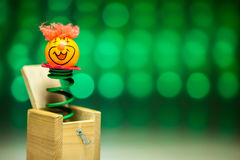 Little clown surprize from wood box. With green background Stock Photo