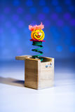 Little clown surprize from wood box. Iwht blue background Royalty Free Stock Image