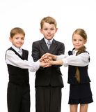 Little colleagues put hands together. Isolated on white. Concept of teamwork and cooperation Royalty Free Stock Photos