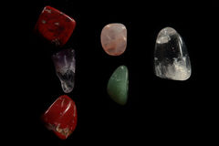 Little colored stones on a black background. Colored and polished stones on a black background stock image