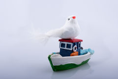 Little colorful model boat with a fake bird Stock Photography