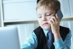 Little confident boss boy in office talks on the phone sitting at the desk with laptop. Young confident executive businessman boss boy in office talks on the royalty free stock images