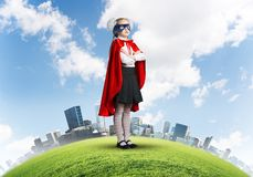 Girl power concept with cute kid guardian against cityscape background stock photo