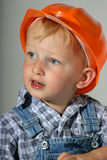 Little construction worker. Cute toddler boy wearing an orange hard hat and pretending to be a little construction worker Royalty Free Stock Photos