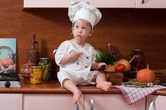 Little cook. Little boy in the cook costume at the kitchen sitting on the table Royalty Free Stock Photos