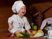 Little cook. Laughing little boy in the cook costume at the kitchen with vegetables Stock Image
