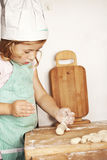 Little cook. Little girl in cook outfit cooking delicious dinner Royalty Free Stock Photography