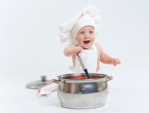 Little cook. Cute little boy in a suit of Food Boy with kitchen accessories. In the studio Royalty Free Stock Image