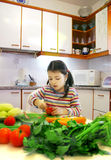 Little cook. Sweet little seven year old girl alone at home, with a table full of vegetables in front of her, ready to make a delicious salad Royalty Free Stock Photos