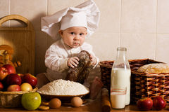 Little cook. Little boy in the cook costume at the kitchen with bread Stock Photos