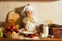 Little cook. Little boy in the cook costume at the kitchen with bread Stock Photography