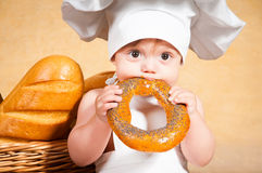 Little cook with a bagel in her hands Royalty Free Stock Photo