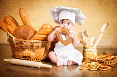 Little cook with a bagel in her hands.  Royalty Free Stock Images