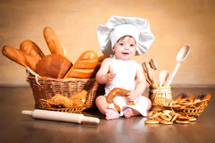 Little cook with a bagel in her hands. Smiling little cook in a chef's hat sitting beside wicker baskets of pastries and bakery products Royalty Free Stock Photo