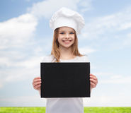 Little cook or baker with blank black paper Stock Photo