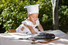 Little cook and big fish. Sweet baby in cook hat preparing big fish stock photography