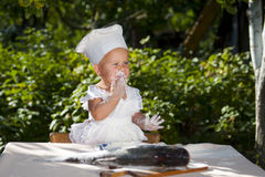 Little cook and big fish. Cute little cook is tasting the flour for fish stock photo