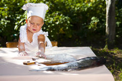 Little cook and big fish. Cute little baby extends to the board and wants to cook fish stock photography
