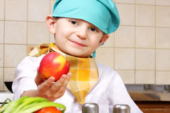 Little cook boy giving red apple Stock Photos
