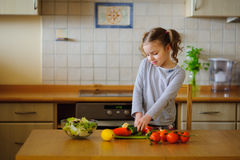 Little cook cooks salad. On a table various vegetables. Royalty Free Stock Photos