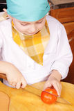 Little cook with cutting tomato Royalty Free Stock Photos