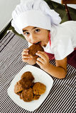 Little cook eating Royalty Free Stock Image