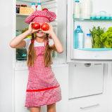 Little cook girl holdin tomatoes like eyes Stock Images