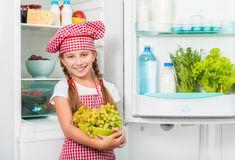 Little cook girl holding grapes Royalty Free Stock Photography