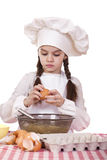 Little cook girl in a white apron breaks eggs in a deep dish Stock Photo