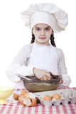 Little cook girl in a white apron breaks eggs in a deep dish Royalty Free Stock Images