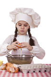 Little cook girl in a white apron breaks eggs in a deep dish Royalty Free Stock Image