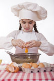 Little cook girl in a white apron breaks eggs in a deep dish Royalty Free Stock Photo
