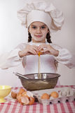 Little cook girl in a white apron breaks eggs in a deep dish Stock Image