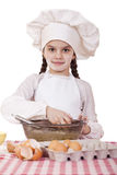 Little cook girl in a white apron breaks eggs in a deep dish Stock Photos