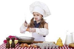 Little cook girl in a white apron breaks eggs in a deep dish Royalty Free Stock Photography