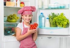 Little cook holding tomatoes near fridge Stock Images