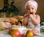Little cook licking a spoon stock photography