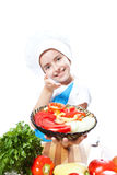 Little cook with a plate of salad and vegetables Royalty Free Stock Photos