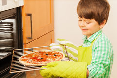 Little cook preparing tasty pizza in the kitchen Stock Images
