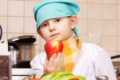 Little cook with red apple Royalty Free Stock Photos
